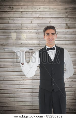 Young waiter presenting a silver tray against wooden planks background