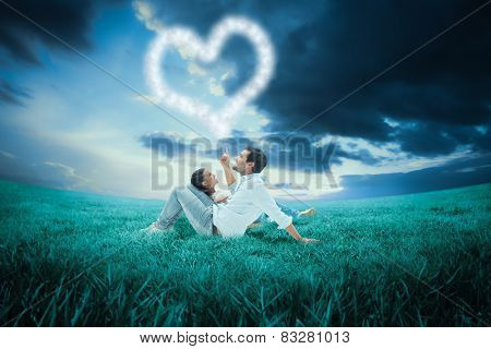 Attractive young couple lying down against blue sky over green field