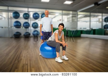 Full length portrait of a happy fit couple against large empty fitness studio with shelf of exercise balls