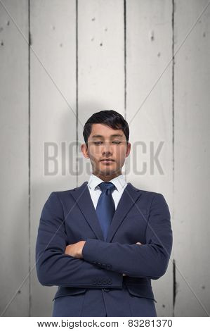 Unsmiling asian businessman with arms crossed against white wood