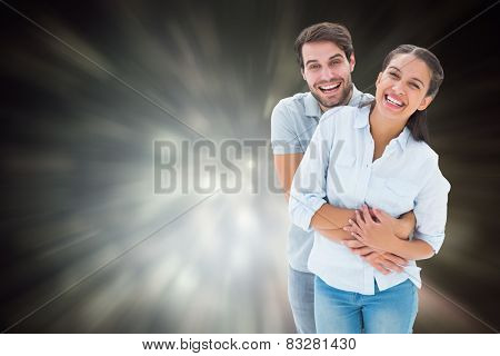 Cute couple hugging and smiling at camera against black abstract light spot design