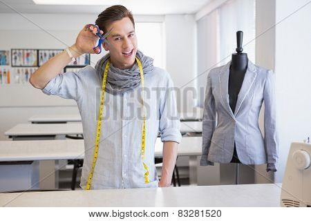 Smiling student holding pair of scissors at the college
