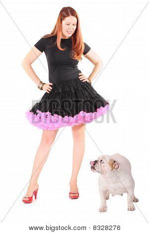 beautiful woman wearing dress is looking at english bulldog.