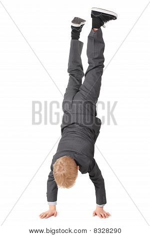little boy wearing suit and sneakers doing handstand. isolated.