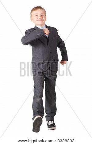 joyful schoolboy wearing accurate suit is walking.