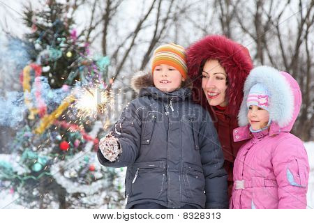 mother and her two children is standing near christmass tree