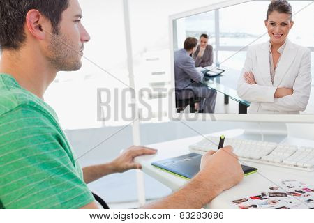 Smiling marketing manager standing in conference room against concentrated photo editor working on graphics tablet