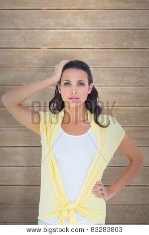 Confused brunette looking at camera against wooden planks