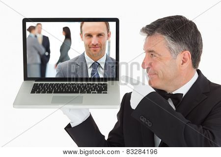 Proud manager posing in front of his team against waiter pointing to laptop