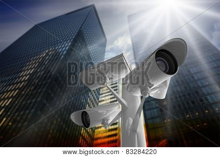 CCTV camera against low angle view of skyscrapers at sunset