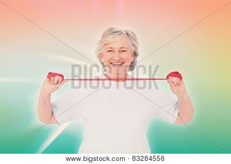 Senior woman using resistance band against abstract background
