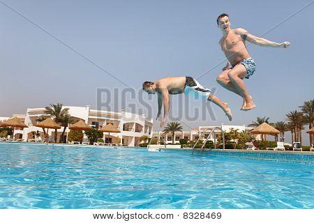 Two Men Jumping In Swimming Pool