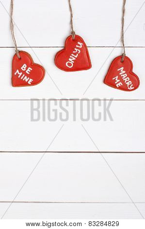 Red cookies in a shape of heart on a wooden table
