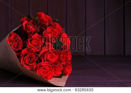 Bouquet of red roses wrapped in paper on wooden background