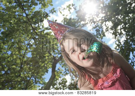 A little girl outside with birthday hat and trumpet