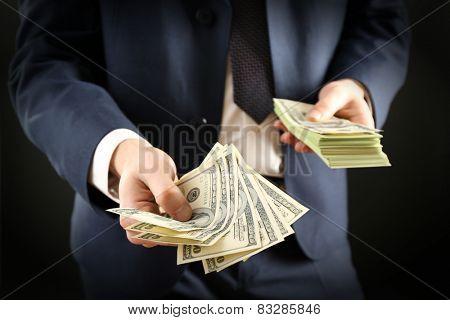 Businessman giving money on dark background