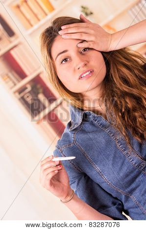 nervous young girl holding pregnancy test