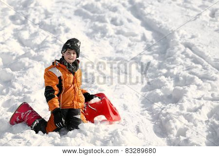 Child Plays With Red Sled In The Snow