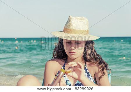 Girl with straw hat applying sun block cream
