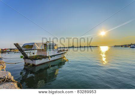 Fishing boat at harbor at sunset