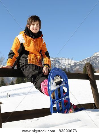Child With Snowshoes In The Mountains In Winter