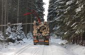 stock photo of logging truck  - Truck with log in road in forest in winter - JPG
