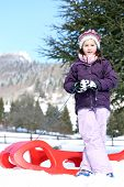 picture of sled  - cute girl plays with the Red sled on the snow in the winter in the mountains - JPG