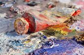 stock photo of dirty  - Closeup of old oil paint tube with red colour lying on dirty artistic palette background for creative art design - JPG