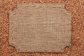picture of stitches  - Figured frame with burlap and stitches with place for your text lying on buckwheat grains as a background - JPG