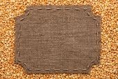 stock photo of stitches  - Figured frame with burlap and stitches with place for your text lying on pea grains as a background - JPG