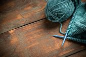stock photo of knitting  - Woollen thread and knitting needle on wooden background - JPG