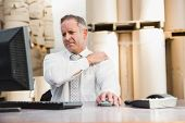 foto of muscle pain  - Warehouse manager suffering from shoulder pain in a large warehouse - JPG