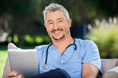 pic of male nurses  - Portrait of smiling male doctor with tablet computer sitting at nursing home porch - JPG