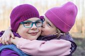 image of three sisters  - Younger sister lovingly kissing her older sister - JPG