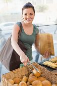 pic of bread rolls  - Pretty brunette picking out bread roll at the bakery - JPG