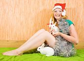 picture of tawdry  - teenager girl in new year decoration with two pet rabbits - JPG