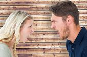 picture of outrageous  - Angry couple shouting during argument against wooden planks background - JPG