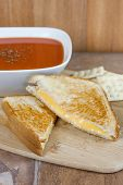 picture of tomato sandwich  - A grilled cheese sandwich with a bowl of tomato soup and saltine crackers on a wooden serving board.