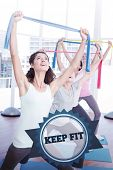 picture of senior class  - The word keep fit and class holding up exercise belts at yoga class against badge - JPG