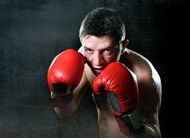 picture of boxers  - young man training shadow boxing with red fighting gloves posing in boxer stance with angry rage face expression isolated on black grunge dirty background - JPG