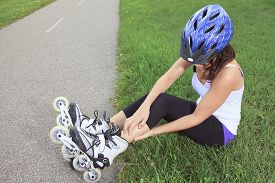 stock photo of inline skating  - A Roller skating girl in park rollerblading on inline skates - JPG