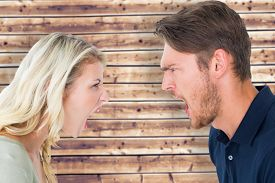foto of angry  - Angry couple shouting during argument against wooden planks background - JPG