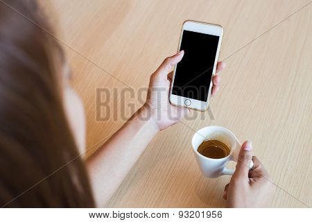 Woman Using A Touch Screen Of White Smartphone On The Wooden Table And Hand Holding Aromatic Cappucc