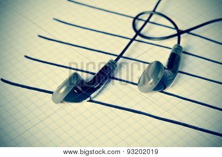 a pair of earphones placed on a staff drawn on a notepad simulating musical notes, with a slight vignette added