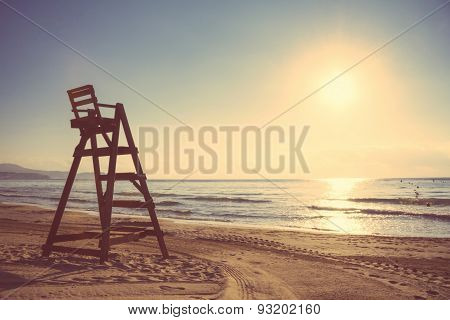 Baywatch chair in empty beach at sunset