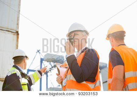 Female supervisor using walkie-talkie while workers discussing in background at shipyard