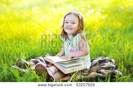 Portrait Of Little Smiling Girl Child With Book Sitting On The Grass In Sunny Summer Day