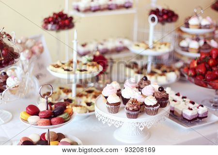 Delicious cupcakes and macaroons on candy bar