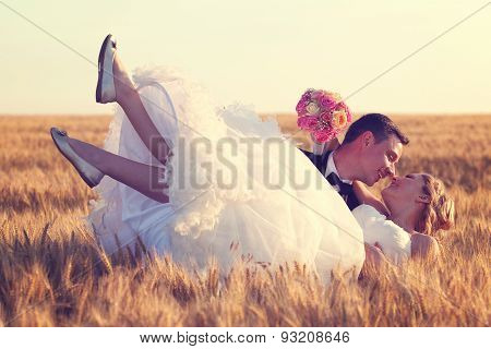 Happy bridal couple in field