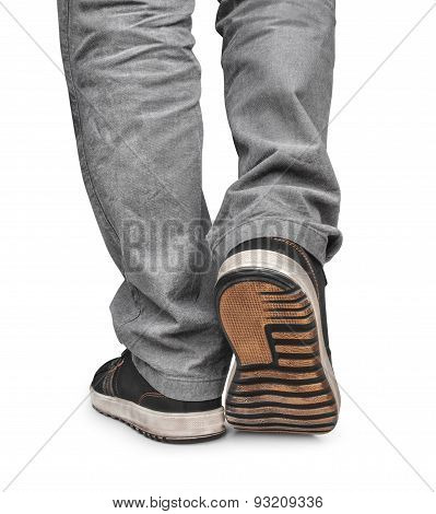 Guy Goes In Black Sneakers And Gray Jeans  Isolated On White Background